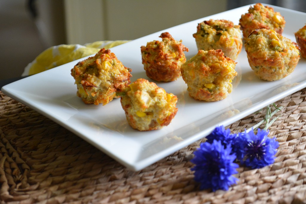 Savoury mini muffins on a white plate with cornflowers in foreground