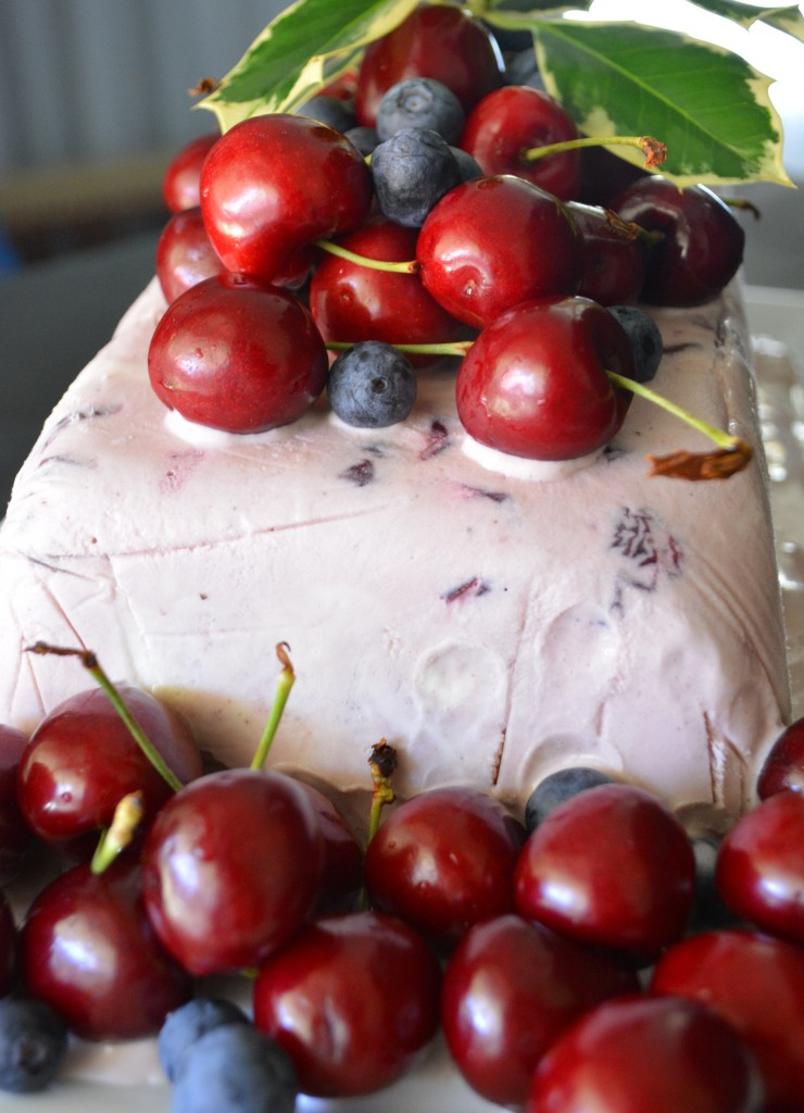 Christmas icecream cake with cherries, berries and holly