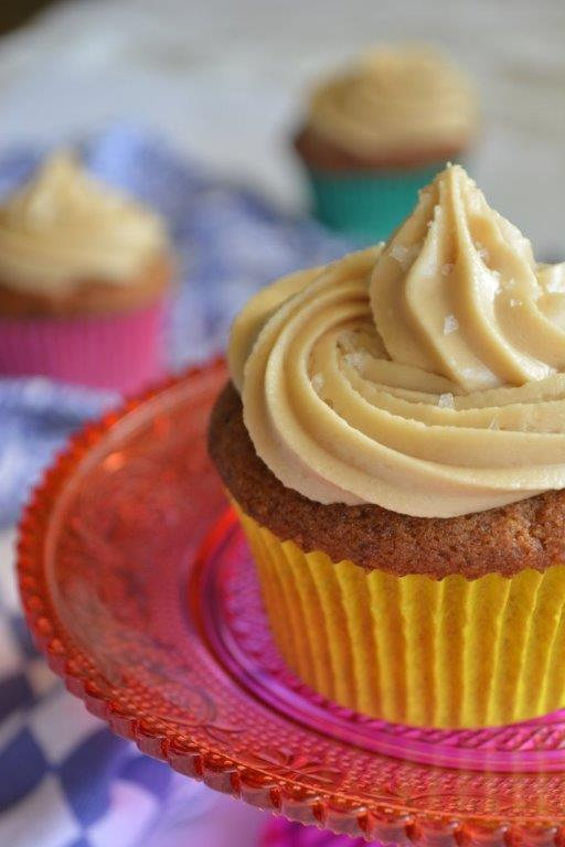 gluten-free sticky date cupcake with butterscotch icing on orange cake stand with blue teatowel in background