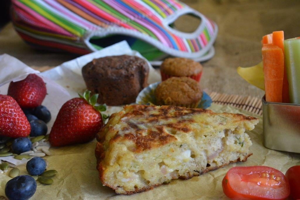 Zucchini, bacon and feta quickbread from with fruit, vegetables and a lunchbox in the background