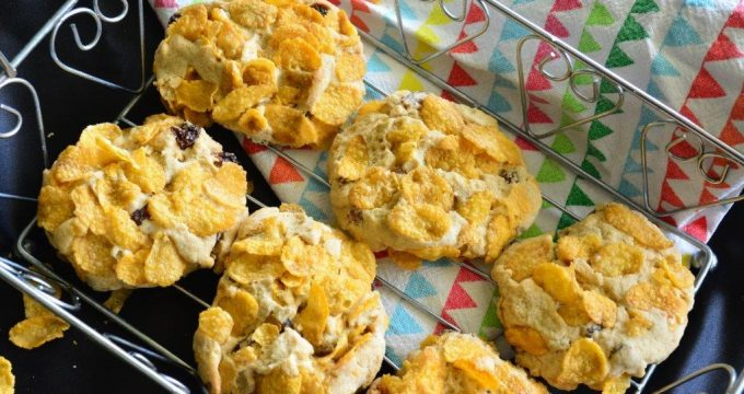 Six gluten-free cornflake cookies in wire basket with multicoloured tea towel, flat-lay view