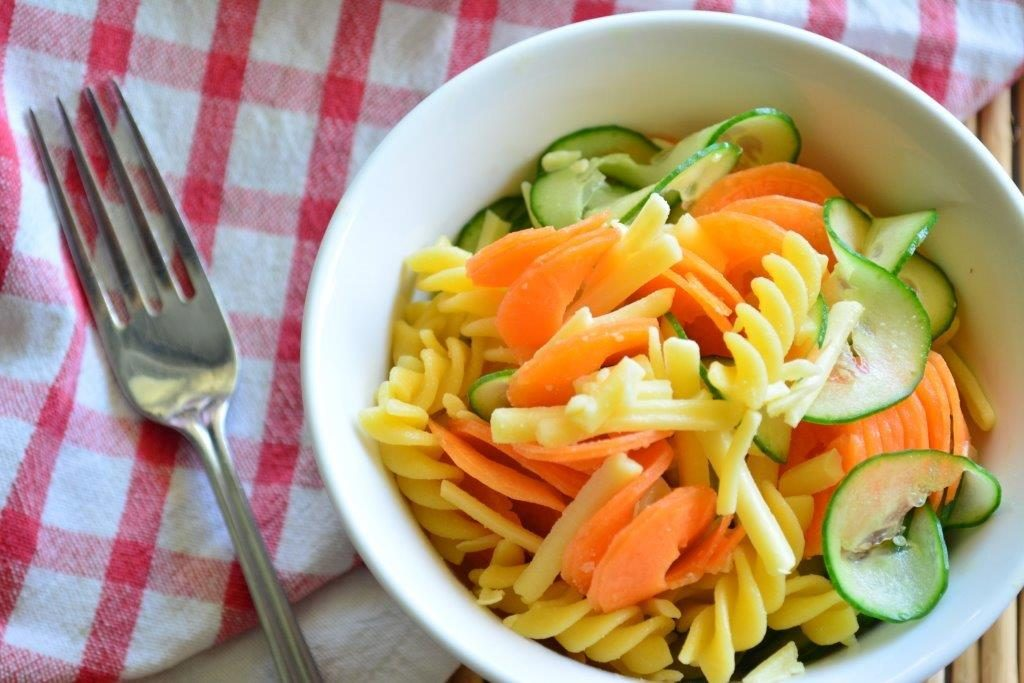 Bowl of gluten-free ribbon salad with a fork and red checked cloth in background