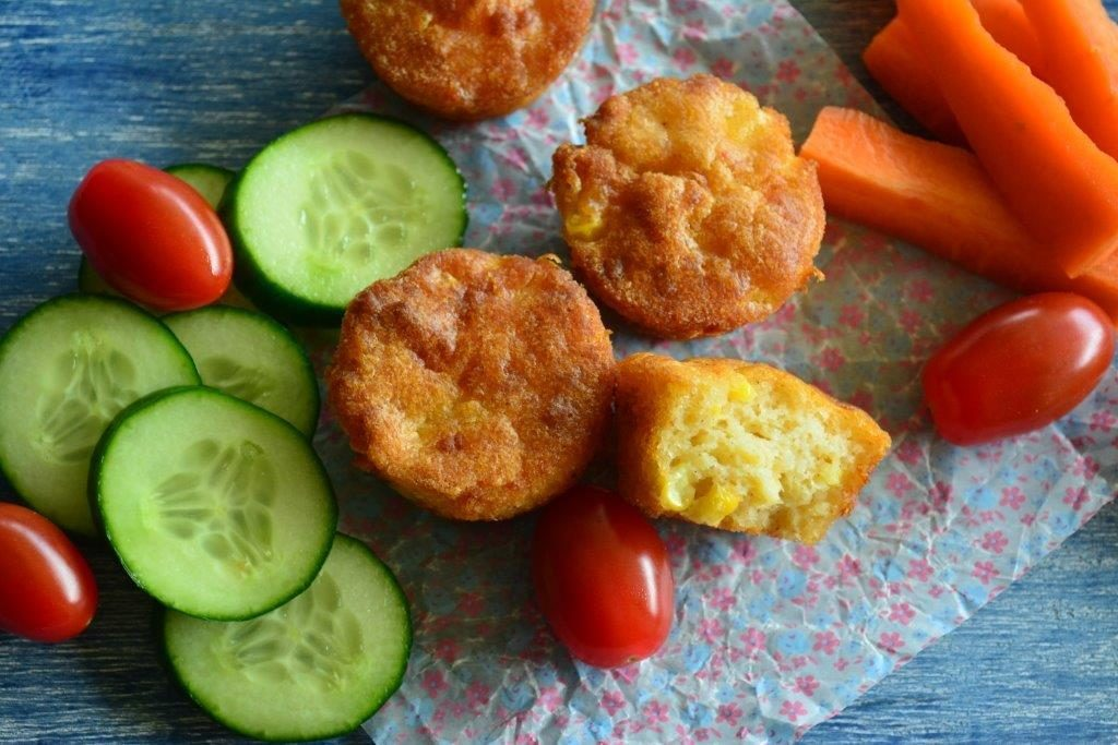 Gluten-free cheese and corn puffs with cucumber, cherry tomatoes and carrot sticks