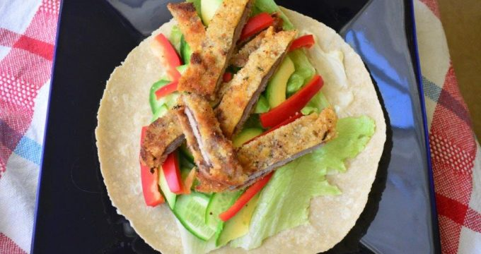 Gluten-free beef schnitzel open wrap with red capsicum and lettuce